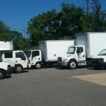 multiple moving trucks and vans lined up for moving services in new york and long island